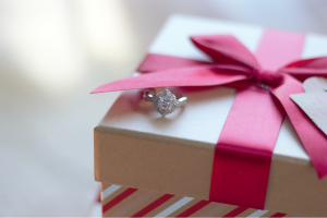 Vintage style white gold diamond engagement ring sits atop a holiday gift box under red ribbon.