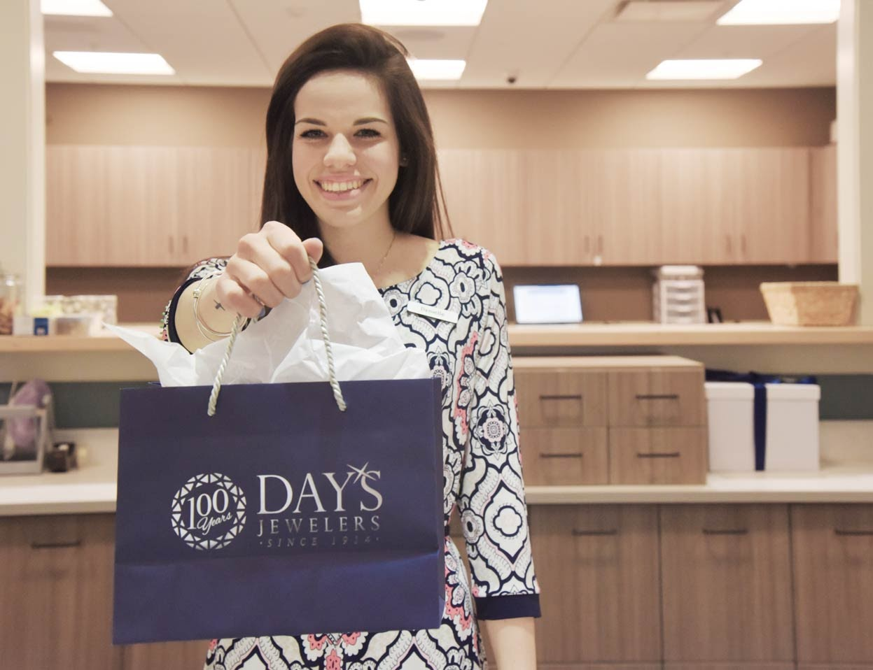 woman holding out Days jewelers shopping bag
